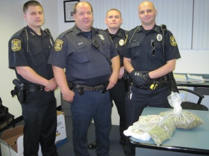 From left to right, Officers Thomas Hickman, Robert Kelch, Craig Brna, and John Bettendorf following a drug bust and seizure of over $49,000.