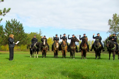 Huron Township Clerk Kathlene Van Wasshnova swears in the eight officers and their horses.