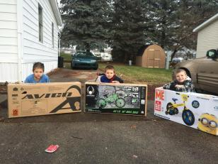 (Left to right) Nine year old Joseph, seven year old Brevin and eight year old David, all Huron residents, smiling big next to their new bikes. (photo/Huron Police)