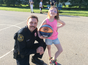 Community Policing Officer Phil Czernik presents a basketball to a young resident in Huron Township. Photo courtesy of the Huron Township Police Department.
