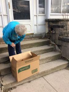 A senior citizen in Huron receives a holiday food basket. Photo courtesy of the Huron Township Historical Society.